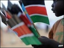 Sudanese street child picks up flags from election campaigning