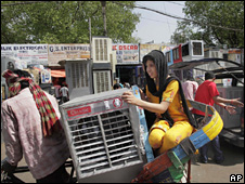 A resident of Delhi carries a water cooler home
