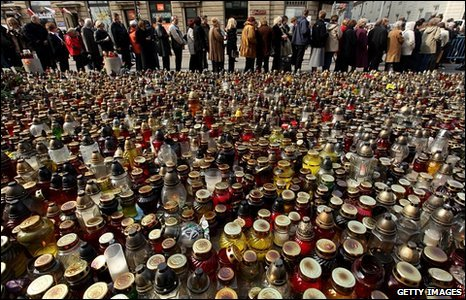 People wait in line to sign books of condolence next to a sea of candles left by mourners outside Warsaw's presidential palace, Poland, 12 April 2010
