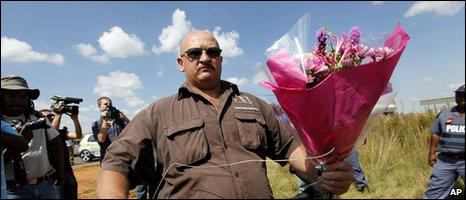 A follower of the Afrikaner Resistance Movement (AWB) leader Eugene Terreblanche brings flowers to leave at the gate of his property near Ventersdrop, 140km West of Johannesburg, South Africa
