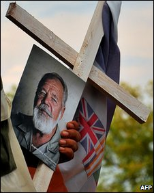 An Afrikaner Resistance Movement (AWB) member holds a picture of AWB leader Eugene Terreblanche and an AWB flag tied to a cross during his funeral at a church in Ventersdorp