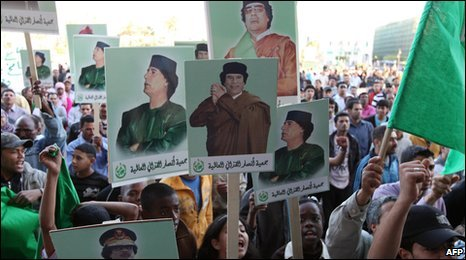 Libyan demonstrators hold pictures of Colonel Gaddaffi