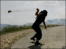 Palestinian hurls rock, Bilin, West Bank (09.04.10)