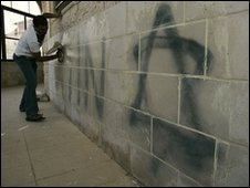 A man cleans grafitti off the wall of a mosque in the West Bank
