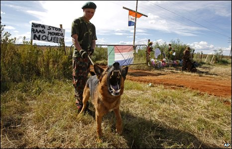 A dog (held on a lead by a private security company guard) reacts outside slain white supremacist leader Eugene Terreblanche's farm situated on the outskirts of Ventersdorp, South Africa