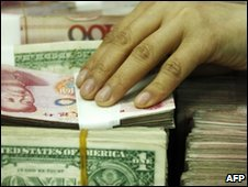 A bank clerk counts US dollars and Chinese yuan