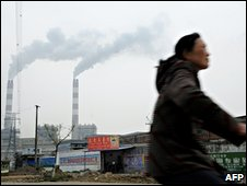 A man rides a bicycle past a factory in Pinghu