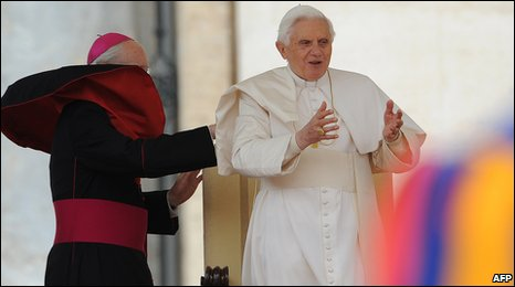 A bishop adjusts the robe of Pope Benedict XVI (R) during his weekly audience in St Peter square at the Vatican on April 14, 2010