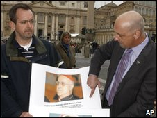 John Pilmaier from Milwaukee, left, and Peter Isely of the SNAP bureau (Survivors Network of those Abused by Priests) show pictures of Pope Benedict XVI, left, and of cardinal Tarcisio Bertone during a press conference in front of the Vatican Thursday, March 25, 2010