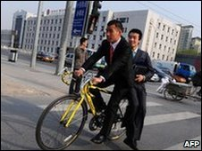 Two men share a 10-speed racing bike to commute through Beijing, April 2010