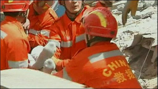 Rescuers pull a survivor from rubble of a hotel