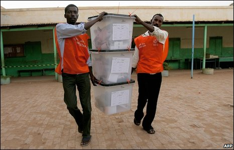 Sudanese polling staffers collect sealed ballot boxes from a polling station at the end of voting in the capital Khartoum on April 15, 2010.