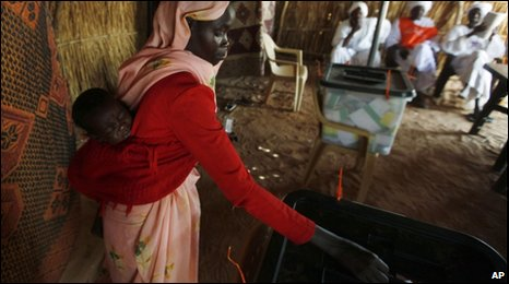 A Sudanese woman cast while carrying a child, at a polling station in the camp of Zamzam, on the outskirts of Fasher, Darfur