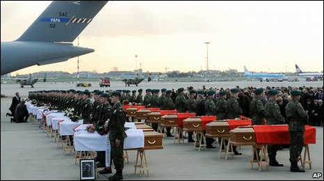 Guards flank the coffins of 34 victims at Warsaw's military airport after their return from Russia, 15 April