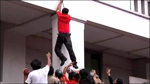 Red-shirt Arisman Pongruanrong uses a cable to climb down from the hotel