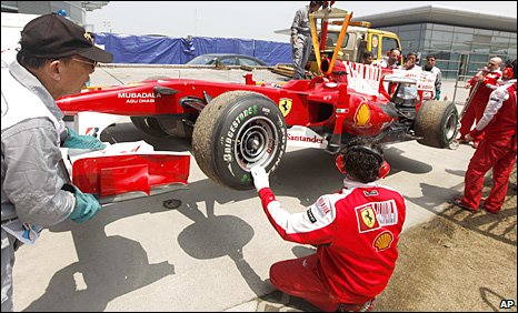 Fernando Alonso's Ferrari is lifted off the circuit in Shanghai