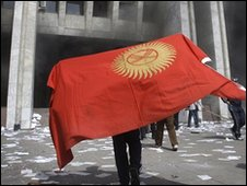 A protester draped in a Kyrgyz national flag walks in front of Kyrgyz government HQ