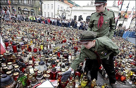 Polish scouts arrange flowers left by mourners at the presidential palace in Warsaw