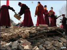 Tibetan Buddhist monks help clear debris amid the rubble of quake demolished buildings in Jiegu