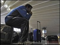 A Spanish passenger rests on top of his baggage at Bilbao airport, northern Spain, 18 April