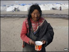 A woman carries instant noodles outside a tent city in Yushu on 19 April 2010
