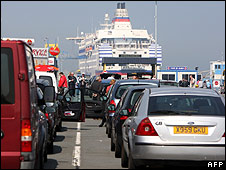People at Ouistreham harbour in north-west France queue to board a ferry bound for England on 19/04/2010