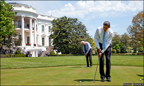 Barack Obama and Joe Biden (background) play golf on the White House lawn (24 April 2009)