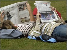 A couple reading the papers in Regents Park, London