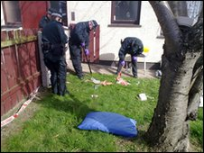Police officers examine the scene of the shooting