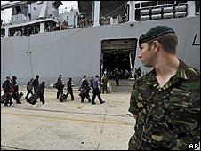 A serviceman watches civilians boarding the HMS Albion in Santander, Spain