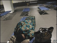 A passenger rests next to her belongings in a dormitory area set up for passengers at Malpensa airport, on the outskirts of Milan