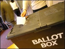 Person casting vote at ballot box