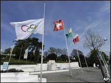 The IOC flag, left, flies at half-mast in front of the IOC headquarters in Lausanne, Switzerland, 21 April 2010