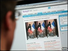 A man in Paris looks at a Yahoo web page featuring a series of photos depicting a man wiping his bottom with the French national flag, 21 April 2010