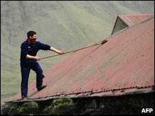 An Icelandic farmer clears ash from the roof of a goat house