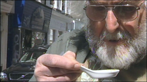 A man looks into a spoon containing a recipe using japanese knotweed