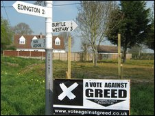 Signpost and vote against greed poster