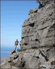 A scientist investigating layering in rocks formed in an ancient magma chamber on the Isle of Rum.
