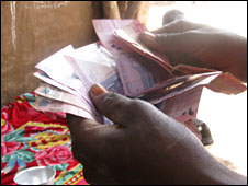 An illegal alcohol brewer in Khartoum counting money