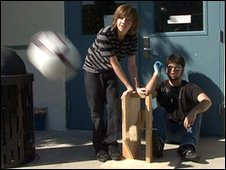 Students projecting a football with a wooden propulsion device prototype