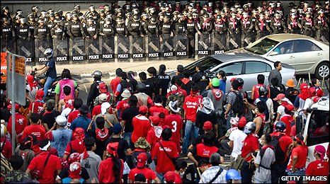 Riot police face red-shirts in their camp in Bangkok's financial district