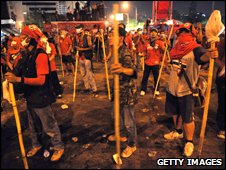 Red-shirt anti-government protesters stand holding bamboo sticks and stones