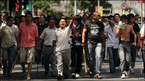 Han Chinese workers armed with sticks and shovels march through Urumqi, 7 July