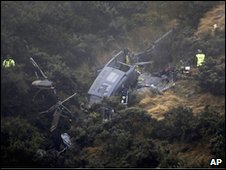 Rescuers stand near the crash site of a Royal New Zealand Air Force helicopter that crashed north of Wellington, 25 April, 2010