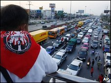 A protester watches as cars back up by a roadblock in central Thailand on 25 April 2010