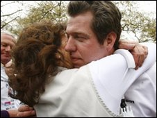 Major Phil Packer hugs a woman