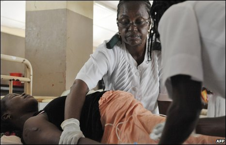 Nurses give aid to a pregnant woman before delivering a baby at the maternity ward of the central hospital in Freetown.