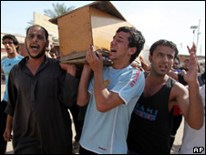Men carry the coffin of a relative killed by a bomb in Baghdad (23 April 2010)