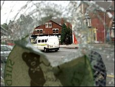 A smashed window and police van