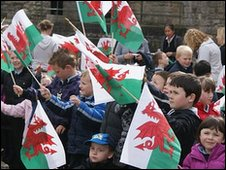 Children wave flags inside the castle
